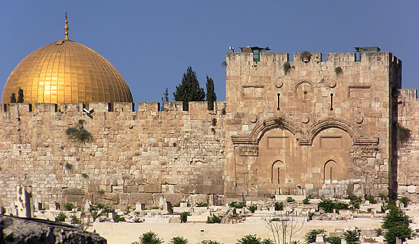 Eastern Gate with Muslim graves before the gate with top of the Dome of the Rock in the background.